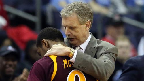 Tim Cluess comforts a basketball player during a game.
