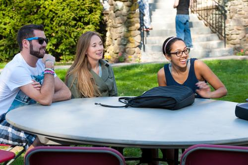 Students sit a table and share a few laughs at a Mission and Ministry hospitality supper.