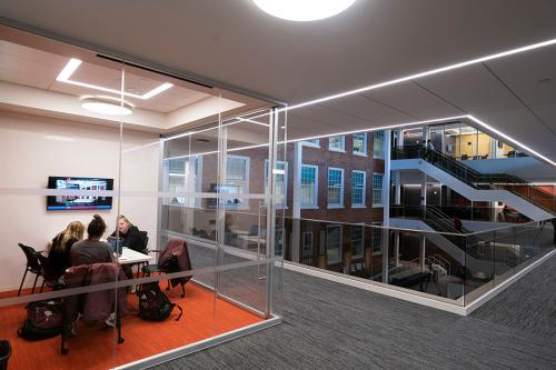 Students study in one of the glass-enclosed spaces at the LaPenta School of Business.