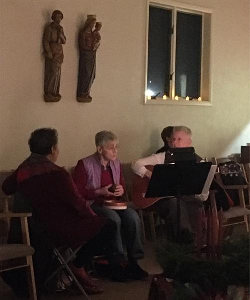 Three people are rehearsing for a choir performance for an Advent mass in the Iona College Chapel.