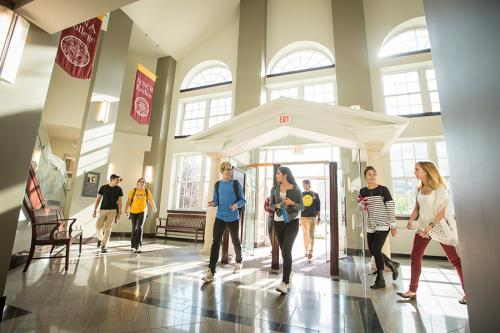 Students enter Ryan Library as beautiful sunlight shines through the glass doors and windows.