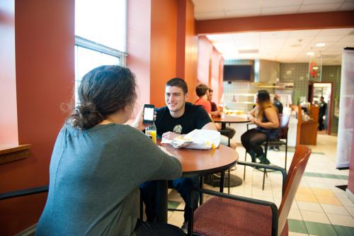 Two students talk at a table while eating lunch in the LaPenta Marketplace.