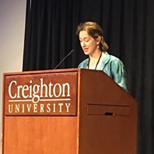 Dr. Erin Lothes stands and speaks at a podium at Creighton University.