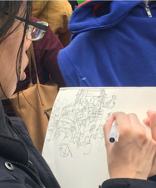 A young person sketches a picture of climate change demonstrators.