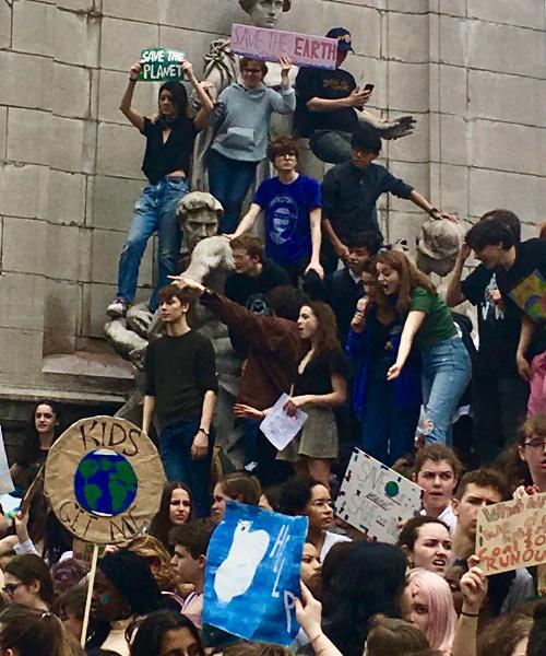 Demonstrators in support of climate change climb up on a statue and hold up posters.