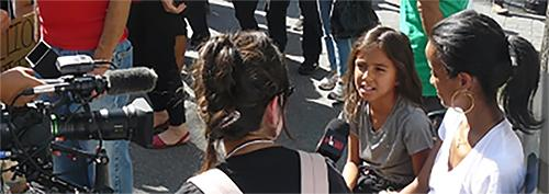 A young girl is interviewed by a journalist.