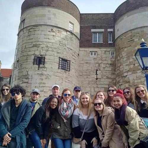 Iona students pose in front of a castle like building in London, England.