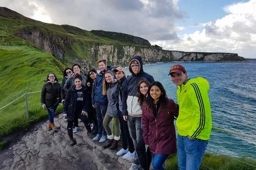 A group of Iona students pose with white cliffs behind them in Ireland.
