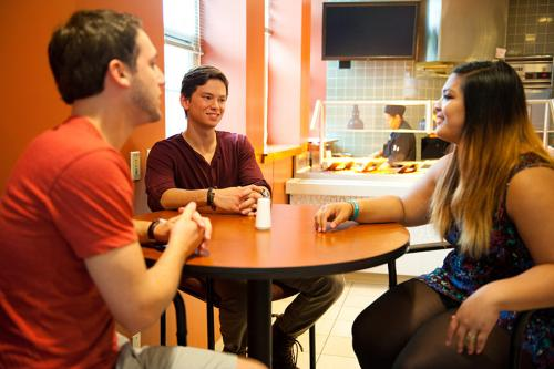 Three students sit at a table and talk in the LaPenta Marketplace.